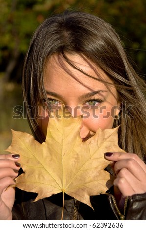 Beautiful young woman holding a maple leaf. Looks into the camera with green eyes. Autumn portrait. - stock photo