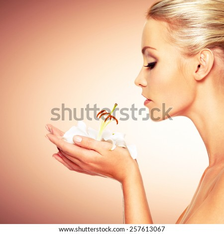 Beautiful young woman holding  a white lily at face - stock photo