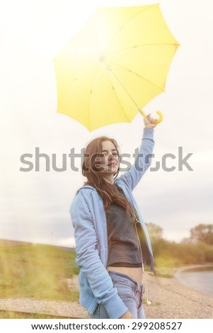 beautiful young woman holding a yellow umbrella against the sun - stock photo