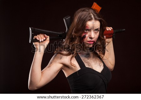 Beautiful young woman holding an automatic assault rifle. With blood on face and wound.  - stock photo