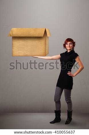 Beautiful young woman holding an empty cardboard box - stock photo