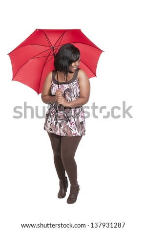 Beautiful young woman holding an umbrella in the rain - stock photo