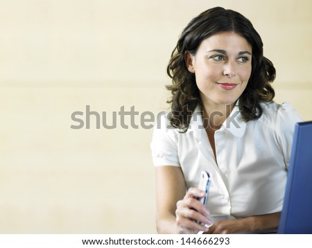 Beautiful young woman holding cell phone while using laptop in office - stock photo