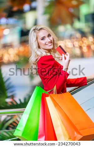 beautiful young woman holding colored shopping bags and credit card in the shopping mall on sales - stock photo