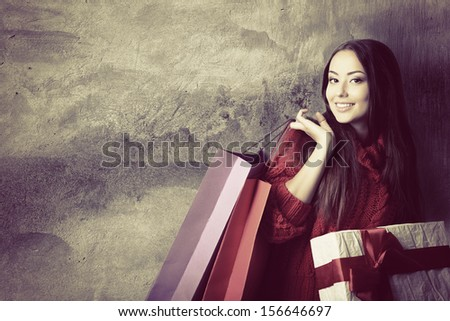 beautiful young woman holding colored shopping bags and gift box over grunge concrete wall, holiday seasonal concept, toned - stock photo