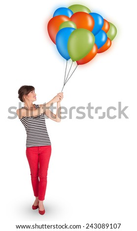 Beautiful young woman holding colorful balloons - stock photo