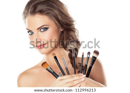 Beautiful young woman holding different make-up brushes, isolated on white - stock photo