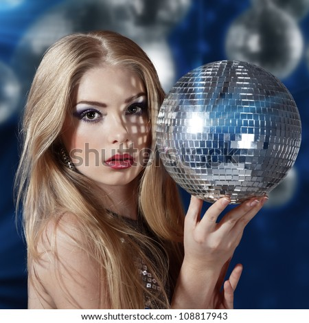 Beautiful young woman holding disco ball at night club - stock photo