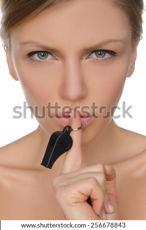 Beautiful young woman holding finger and whistle before lips - stock photo