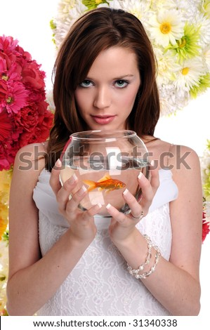 Beautiful young woman holding fishbowl with goldfish over background with flowers - stock photo