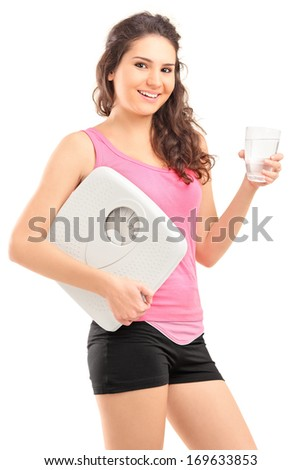 Beautiful young woman holding glass of water and weight scale, isolated on white background - stock photo