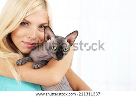 Beautiful young woman holding gray sphinx cat on light background - stock photo