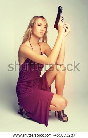 Beautiful young woman holding gun - stock photo
