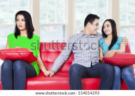 Beautiful young woman holding hands with man sitting near his girlfriend at home - stock photo