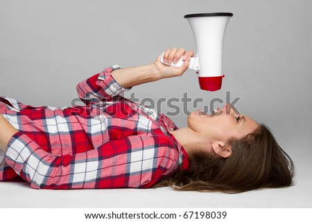 Beautiful young woman holding megaphone - stock photo