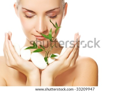 Beautiful young woman holding plant growing up through stones - stock photo