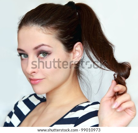 Beautiful young woman holding the long hair with flirting look. Closeup portrait of 20s green eyes girl - stock photo