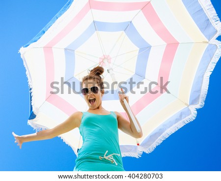 Beautiful young woman holding umbrella over sky - stock photo