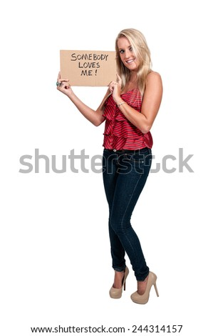 Beautiful young woman holding up an inspirational sign that says somebody loves me - stock photo