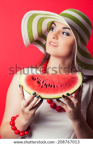 beautiful young woman holding watermelon against red background - stock photo
