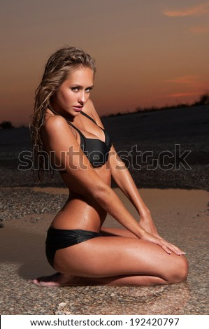 beautiful young woman in a bathing suit sitting on the beach - stock photo
