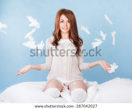 Beautiful young woman in a bed dropping the feathers over blue background - stock photo