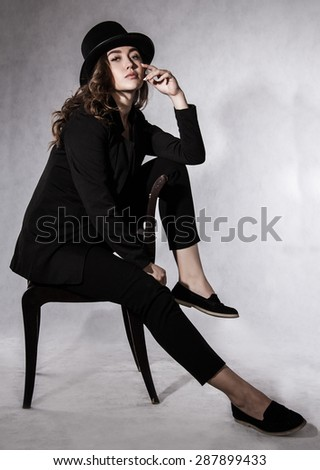 Beautiful young woman in a black hat and a black jacket - stock photo