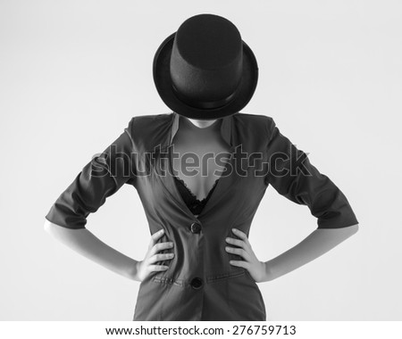 Beautiful young woman in a black hat and jacket with an open neckline. - stock photo