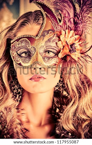 Beautiful young woman in a carnival mask over vintage background. - stock photo