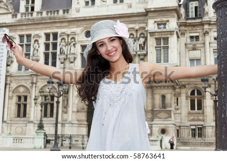 Beautiful young woman in a fashion pose in a Parisian plaza. - stock photo