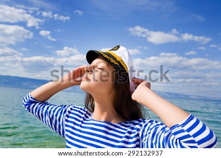 Beautiful young woman in a frock enjoying the sun at the sea. Eyes closed. Copy space. - stock photo