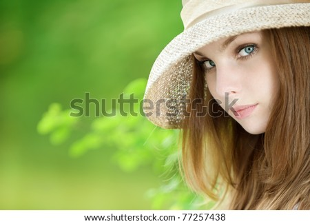 beautiful young woman in a hat on green background - stock photo