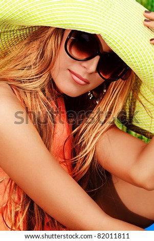 Beautiful young woman in a hat outdoors. - stock photo