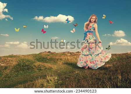 Beautiful young woman in a long dress color walks outdoors. Girl with butterflies. - stock photo