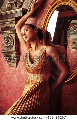 Beautiful young woman in a  luxurious classic interior. - stock photo