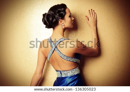Beautiful young woman in a luxurious dress posing against a wall. - stock photo