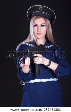 Beautiful young woman in a marine uniform with a submachine gun over black background - stock photo