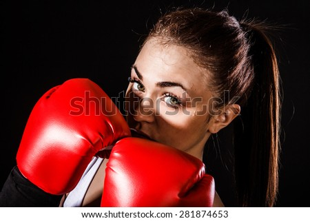 Beautiful young woman in a red boxing gloves over black background - stock photo