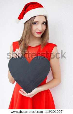 Beautiful young woman in a red Christmas hat and red dress, holding a sign in the form of a heart with empty space for text  over white wall background.  A series of photos in my portfolio. - stock photo