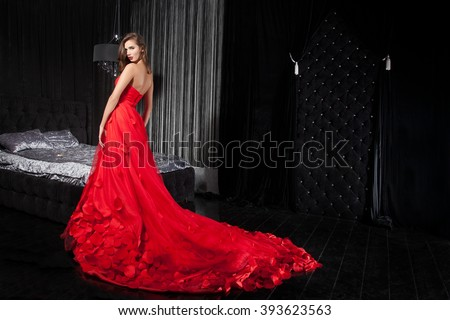 Beautiful young woman in a red dress, the background interior - stock photo