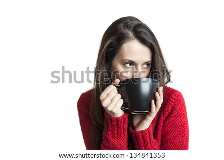 Beautiful young woman in a red sweater drinking coffee from a black cup. - stock photo