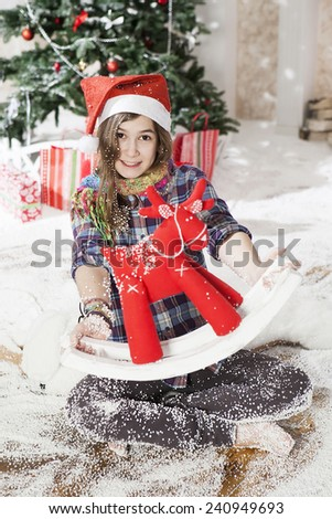 Beautiful young woman in a Santa hat sitting on the floor near Christmas tree - stock photo