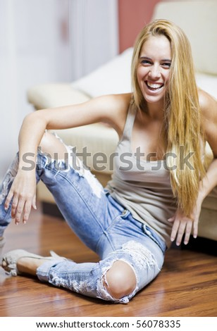 beautiful young woman in a sofa of a livingroom of a house - stock photo