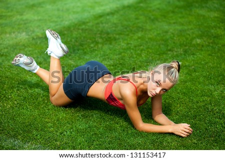 Beautiful young woman in a sports suit lying on a green soccer field at the stadium - stock photo