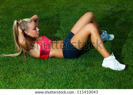 Beautiful young woman in a sports suit working out on the green field of stadium - stock photo