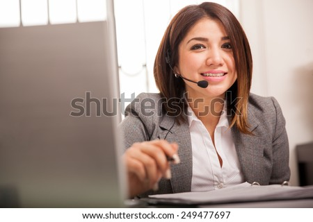 Beautiful young woman in a suit wearing a headset and taking calls from customers - stock photo