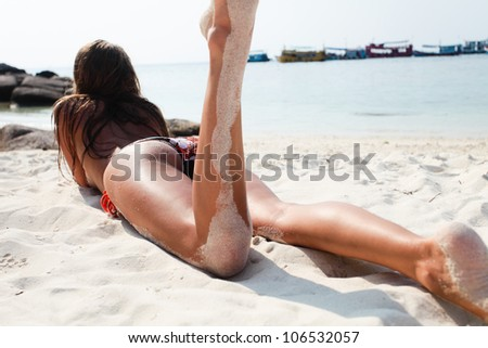 Beautiful young woman in a swimsuit lying on the sand at the beach. View from the back - stock photo