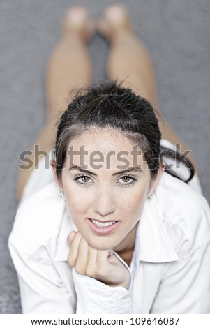 Beautiful young woman in a white shirt lying on her living room floor - stock photo