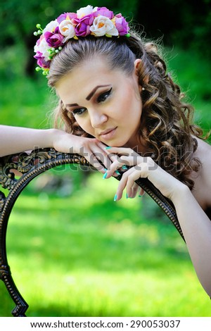 Beautiful young woman in a wreath with vintage mirror outdoors - stock photo