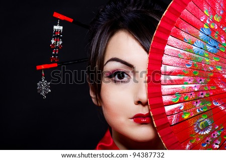 Beautiful young woman in Asian costume with red Asian fan on  background. - stock photo